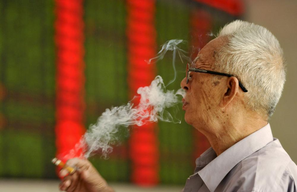 An investor smokes a cigarette in front of an electronic board showing stock information at a brokerage house in Fuyang, Anhui province, China, September 14, 2015. China stocks fell more than 3 percent on Monday morning as lingering concerns over the economy offset optimism that reform among state-owned enterprises (SOEs) would accelerate. REUTERS/Stringer CHINA OUT. NO COMMERCIAL OR EDITORIAL SALES IN CHINA