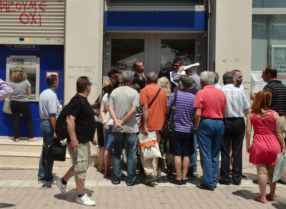 A woman withdraws money from an ATM machine while others speak to an official of the bank in Athens.