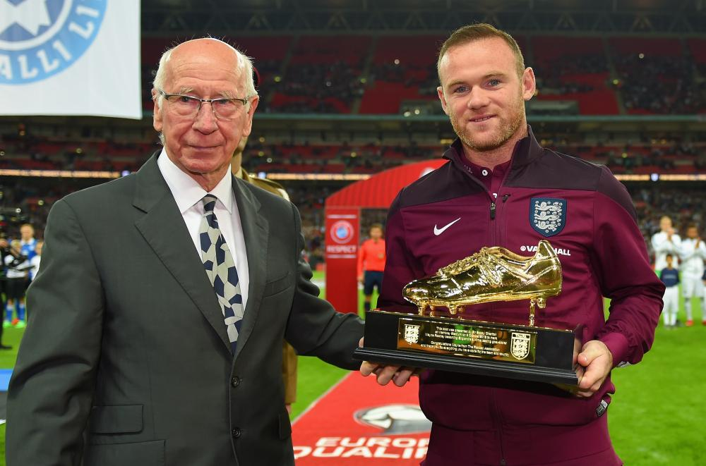 Wayne Rooney is presented with the Golden Boot by Sir Bobby Charlton after breaking his record of 49 goals.