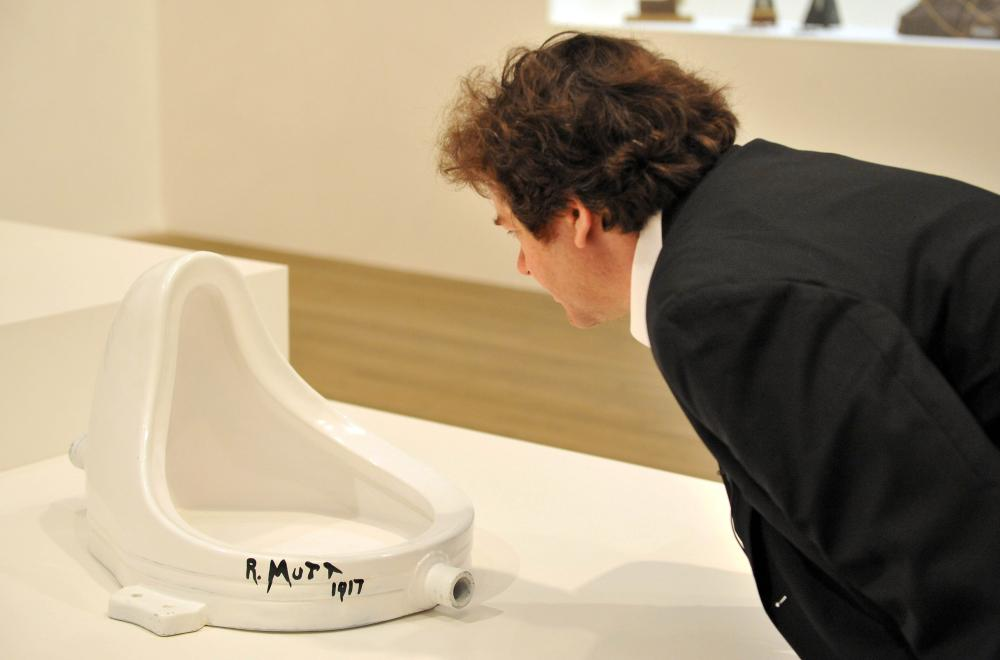 A visitor looks at Fountain (1917) by Marcel Duchamp (1887-1968) - the public urinal that Duchamp transformed into a work of art and is seen as the paradigm of the readymade.