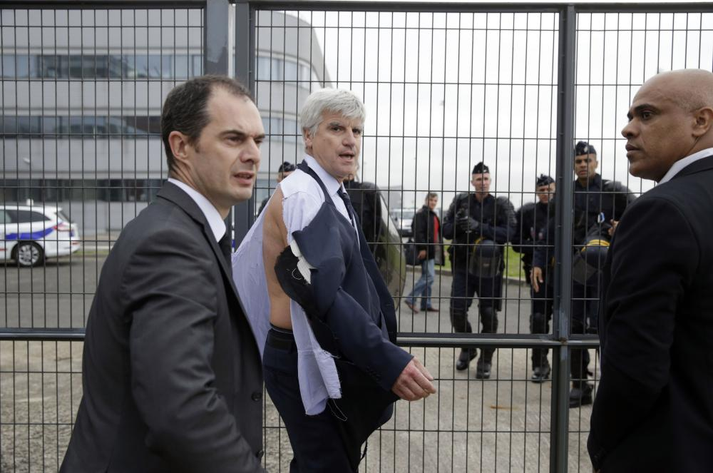 Director of Air France in Orly Pierre Plissonnier, nearly shirtless, walks away from the crowd, helped by security and police officers, after several hundred of employees invaded the offices of Air France, interrupting the meeting of the Central Committee (CCE) in Roissy-en-France, on October 5, 2015. Air France-KLM unveiled a revamped restructuring plan on October 5 that could lead to 2,900 job losses after pilots for the struggling airline refused to accept a proposal to work longer hours. AFP PHOTO / KENZO TRIBOUILLARDKENZO TRIBOUILLARD/AFP/Getty Images
