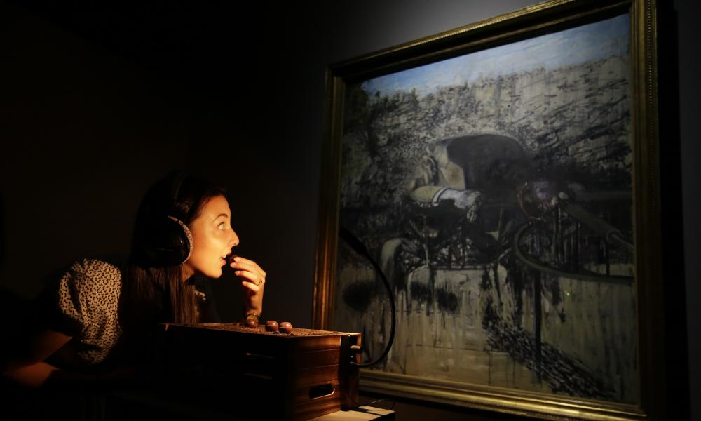 A member of the Tate Britain eats a chocolate in front of a painting by Francis Bacon entitled Figure in Landscape 1945