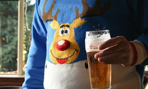 A man with a pint of beer in a Christmas jumper with a reindeer pattern at the Warren Wood pub, Buckhurst Hill, Essex, England<br>CC19B6 A man with a pint of beer in a Christmas jumper with a reindeer pattern at the Warren Wood pub, Buckhurst Hill, Essex, England