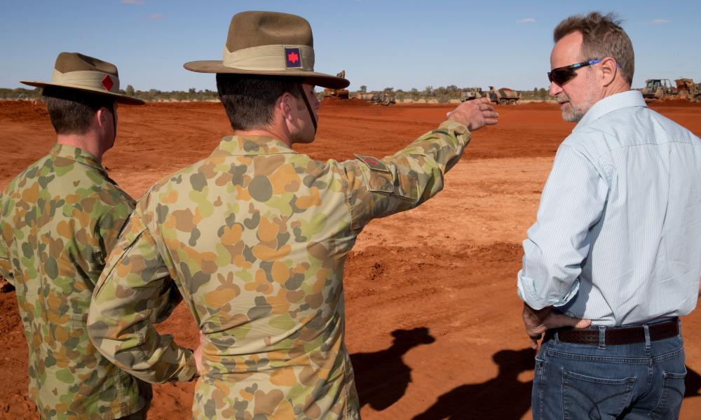 Major Chris Sampson shows the waste treatment system to senator Nigel Scullion, Indigenous affairs minister, and Colonel Stephen Gliddon (left).