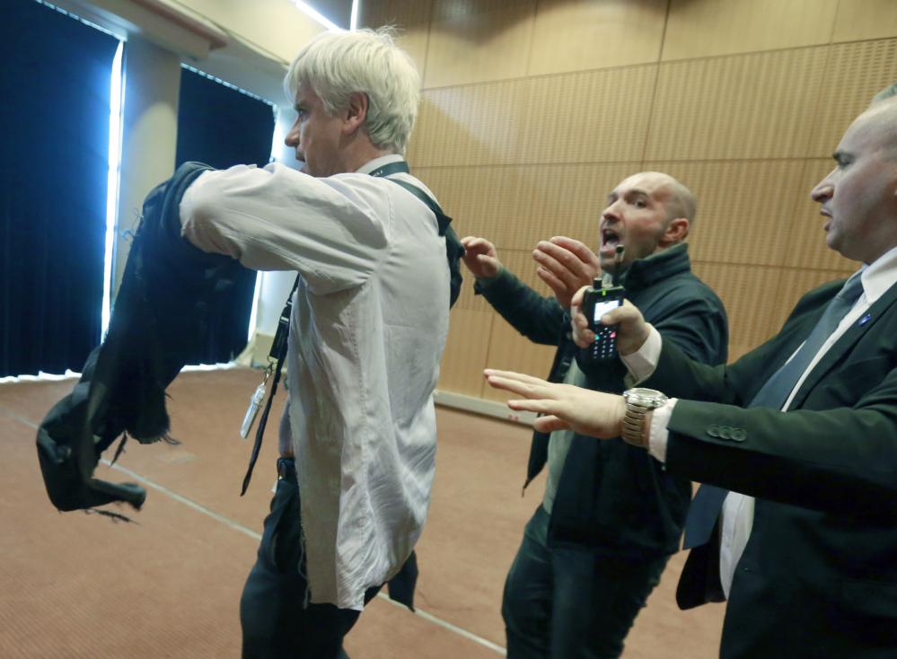 Air France assistant director long-haul flight, Pierre Plissonnier, left, is protected by security guards as he flees the Air France headquarters at Roissy Airport, north of Paris, France, after scuffles with union activists. Monday, Oct. 5, 2015. Union activists protesting proposed layoffs at Air France stormed the headquarters during a meeting about the job cuts, zeroing in on two managers who had their shirts torn from their bodies, scaled a fence and fled under police protection. (AP Photo/Jacques Brinon)
