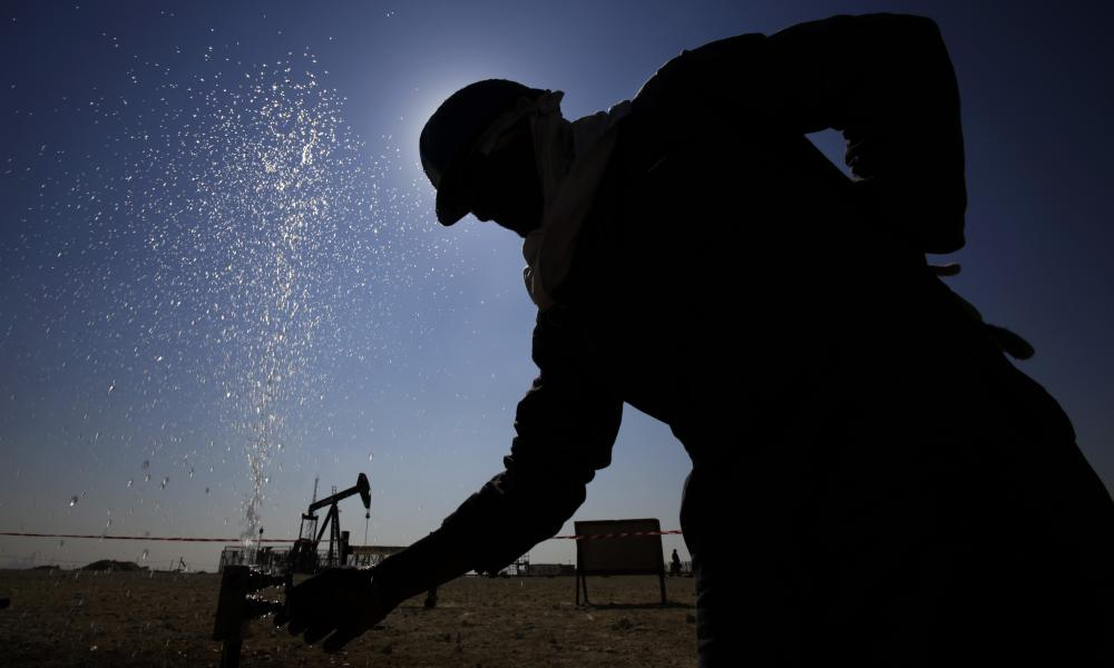 An oil worker adjusts a valve releasing a spray of water while working on oil pipeline in the desert oil fields of Sakhir, Bahrain.