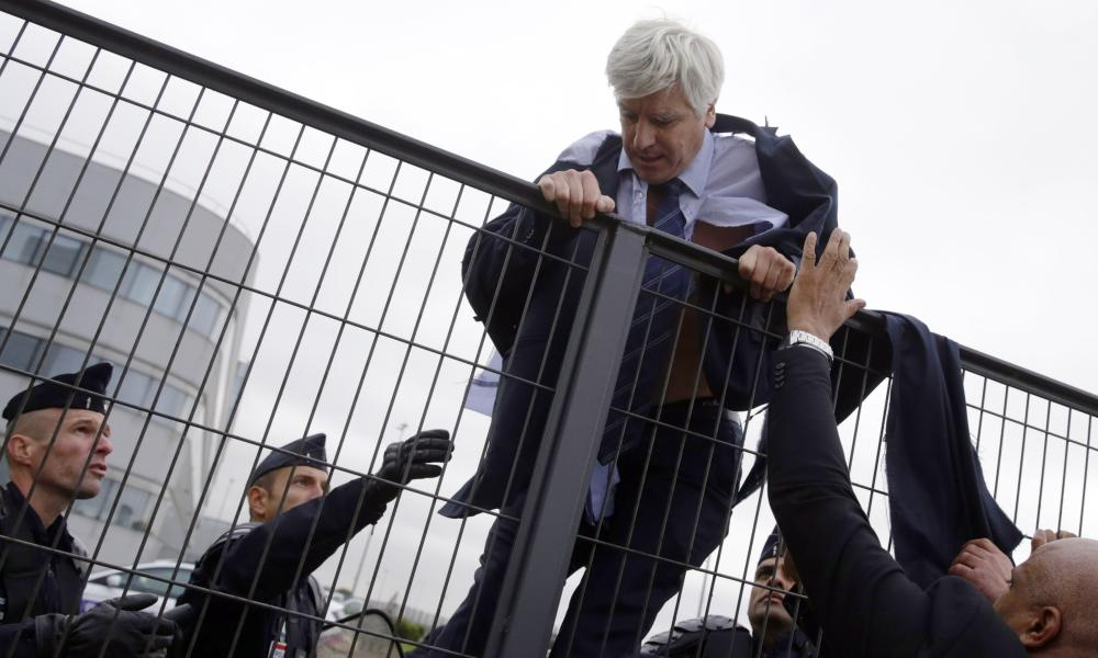 TOPSHOTS Director of Air France in Orly Pierre Plissonnier, nearly shirtless, tries to cross a fence, helped by security and police officers, after several hundred of employees invaded the offices of Air France, interrupting the meeting of the Central Committee (CCE) in Roissy-en-France, on October 5, 2015. Air France-KLM unveiled a revamped restructuring plan on October 5 that could lead to 2,900 job losses after pilots for the struggling airline refused to accept a proposal to work longer hours. AFP PHOTO / KENZO TRIBOUILLARDKENZO TRIBOUILLARD/AFP/Getty Images