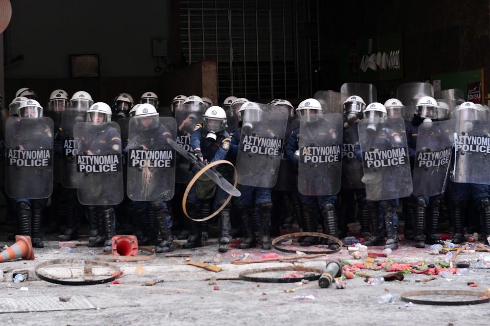 "Farmers throw objects at police blocking the entrance to the Agriculture ministry in Athens, during a demonstration against the pension reform on February 12, 2016 Fears that Greece will exit the eurozone, a ""Grexit"", could revive if Greek authorities do not come up with ""credible"" reforms, notably on pensions, a senior IMF official said February 11, 2016. / AFP / LOUISA GOULIAMAKILOUISA GOULIAMAKI/AFP/Getty Images"