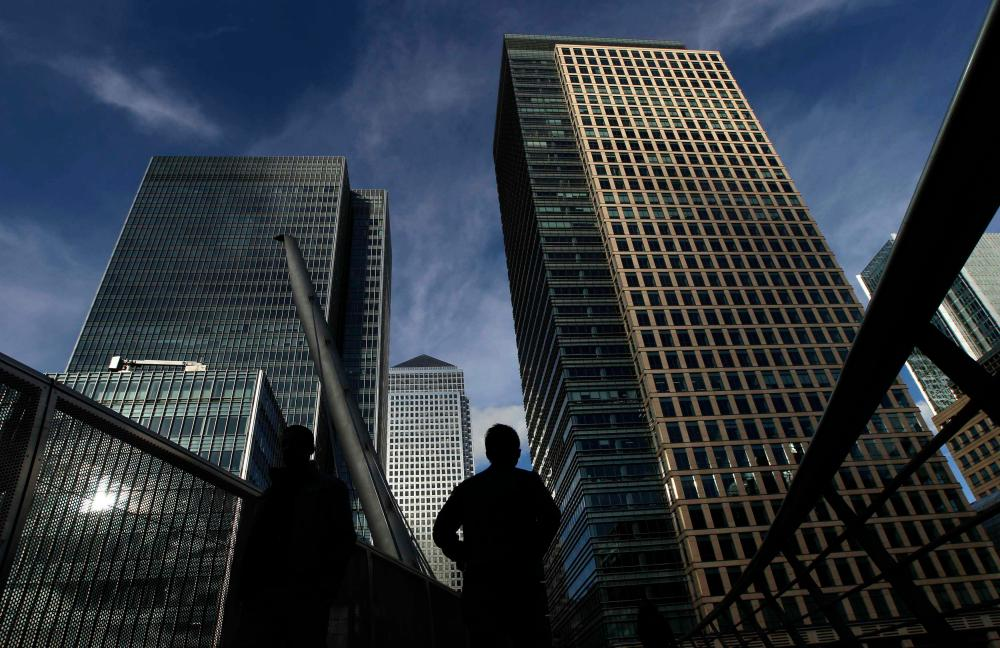 To match Feature BRITAIN-LONDON/Silhouetted workers walk in front of office towers in the Canary Wharf financial district in London February 16, 2011.