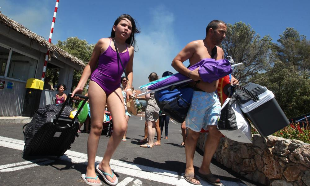 Tourists are evacuated from a campsite near Frejus, south-eastern France, after forest fires broke out nearby.