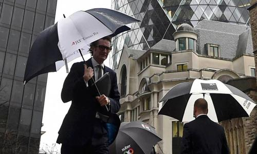 City workers walk in the rain in the financial district of the City of London, Britain January 7, 2016. Global shares tumbled for a sixth day on Thursday and oil prices slid to levels not seen since the early 2000s, after China guided the yuan lower and Shanghai shares tumbled 7 percent in less than half an hour. REUTERS/Toby Melville