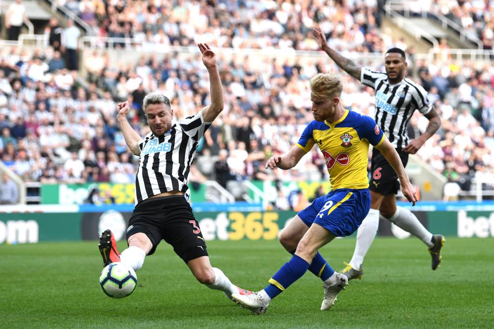 Josh Sims of Southampton sees his shot blocked by Paul Dummett of Newcastle United.