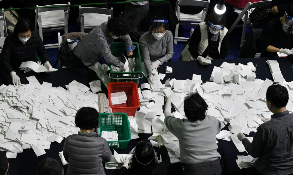 South Korean election officials sort voting papers for ballot counting in the parliamentary elections at a gymnasium in Seoul on 15 April 2020.