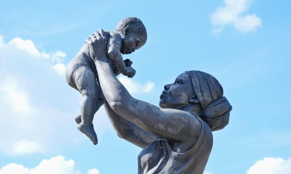 Close-up of a naturalistic bronze statue of a black woman in a headscarf holding a baby up high and looking into its eyes
