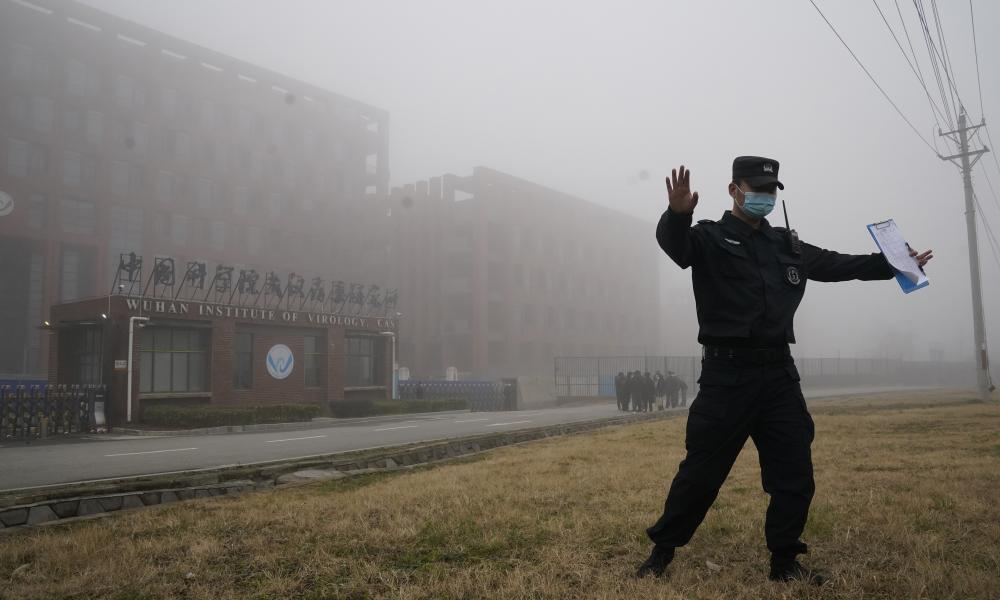 A security official moves journalists away from the Wuhan Institute of Virology after a World Health Organization team arrived for a field visit in Wuhan in China's Hubei province on Wednesday. The WHO team is investigating the origins of the coronavirus pandemic and has visited two disease control centres in Hubei.