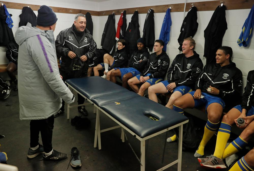 Tom Loizou, Haringey Borough's manager, talks with his first-team squad in the home dressing room before training.