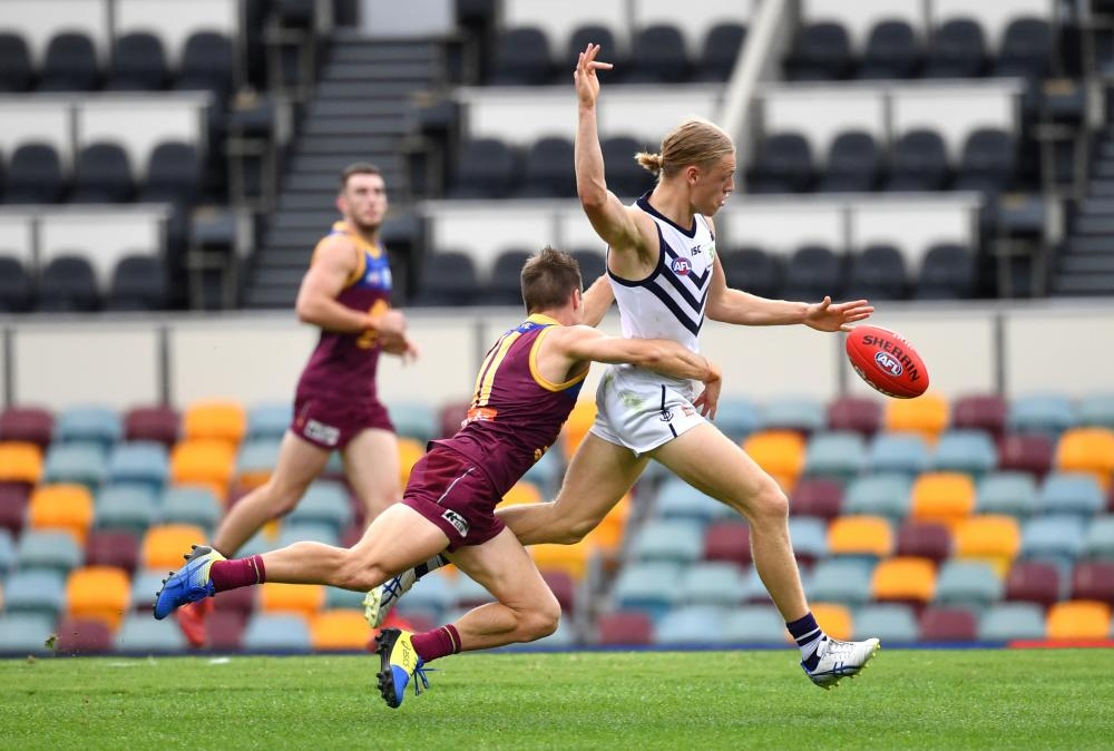 Hayden Young of the Dockers is tackled by Lincoln McCarthy of the Lions.