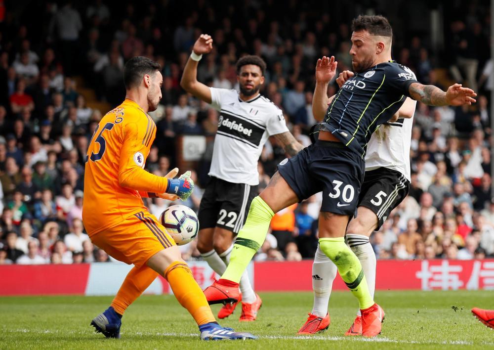 Fulham's Sergio Rico saves from Manchester City's Nicolas Otamendi.