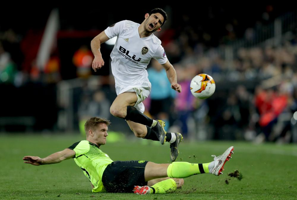 Kristoffer Ajer of Celtic tackles Goncalo Guedes of Valencia.
