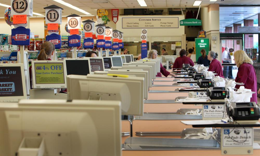 Cashiers and baggers sit idle at the Market Basket supermarket chain in Concord, N.H.