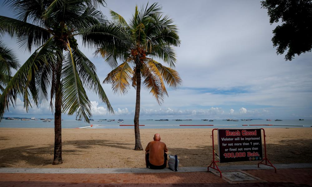 A man sits at the edge of the beach by a left over sign warning of the beach's closure, on the first day of reopening in Pattaya, Thailand.