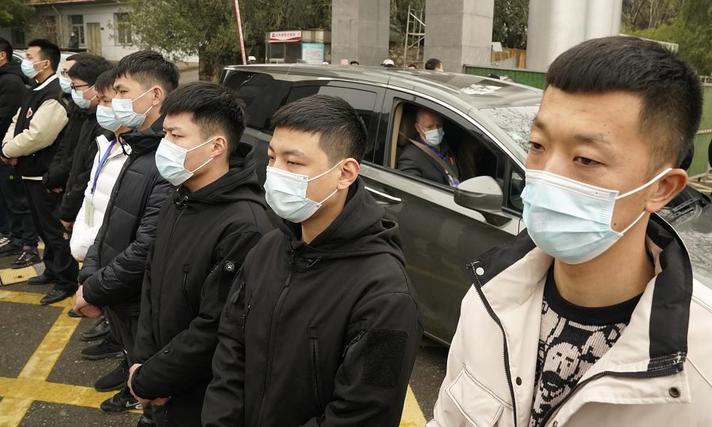 A World Health Organization team member leaves in a car past a row of security personnel at the Hubei Center for Disease Control and Prevention.