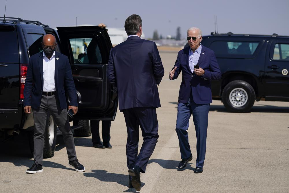 Joe Biden talks with California Gov. Gavin Newsom as he arrived in the state on Monday to survey wildfire damage.