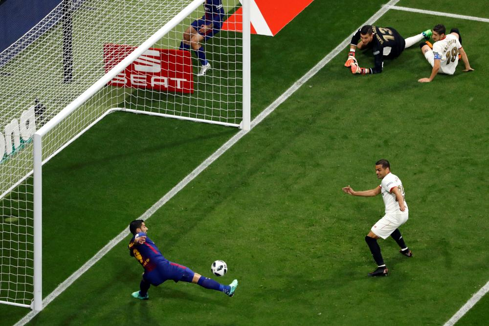 Luis Suárez stretches to put Barcelona ahead against Sevilla in the Copa del Rey final after brilliant work from Philippe Coutinho.