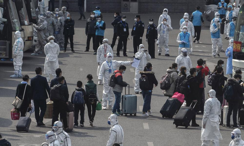 Chinese workers and health officials wear protective white suits as travellers from Wuhan are processed and taken to do 14 days of quarantine, after arriving on the first trains to Beijing on April 8, 2020 in Beijing, China.