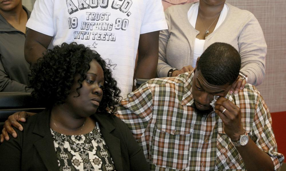 Odell Edwards wipes away tears as he sits with his wife, Charmaine Edwards, in a law office in Dallas on Monday.
