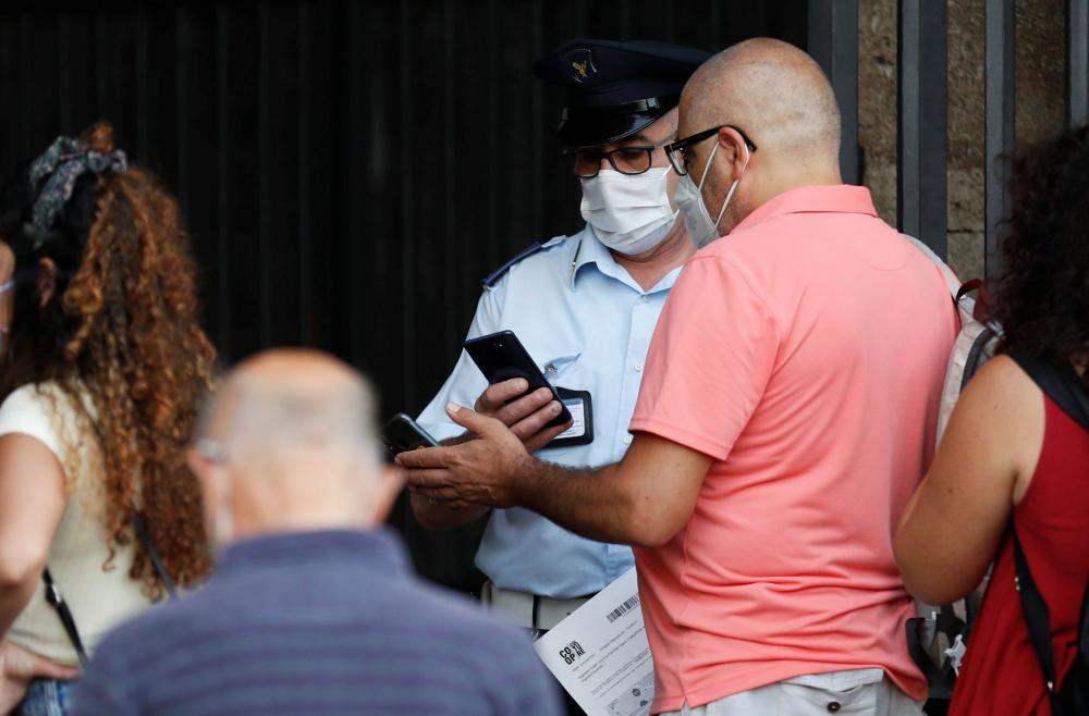 A tourist shows his 'green pass', which records proof of full vaccination, recovery from the virus, or a negative test, as he enters the Colosseum, in Rome, Italy.