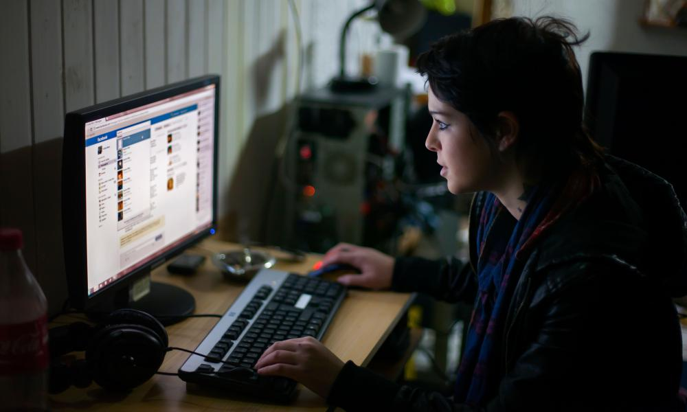 Young woman checking her facebook on a computer