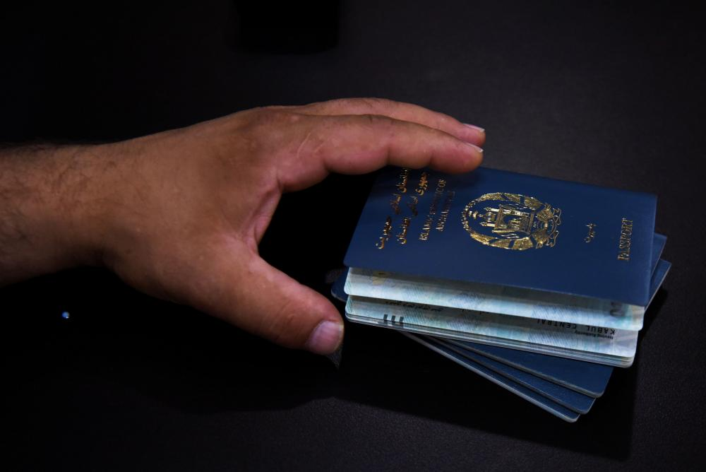 An Afghan man holds his family's passports. The visa lottery program offers a pathway to the US with minimum eligibility requirements.