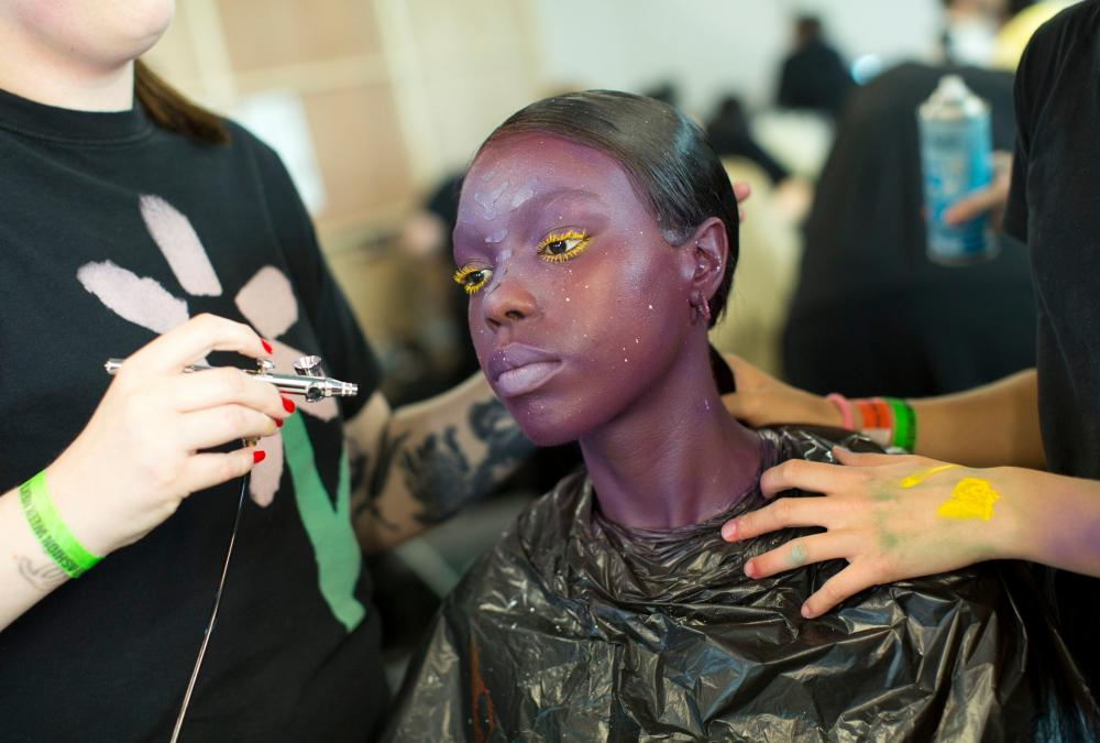 Makeup artists create an avant-garde look on a model for the Charles Jeffrey Loverboy show