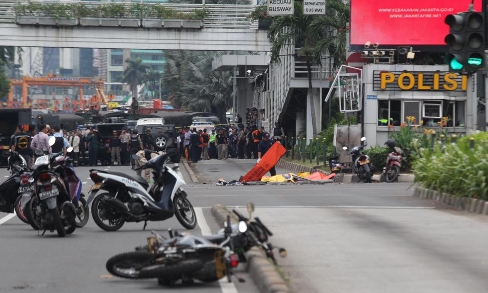 Police cover the bodies of victims of one of the bomb explosions in Jakarta, Indonesia.