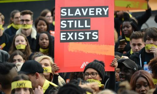 LONDON, UNITED KINGDOM - OCTOBER 14: People marching against modern slavery through London wearing face masks representing the silence of modern slaves in forced labour and sexual exploitation on October 14, 2017 in London, England.