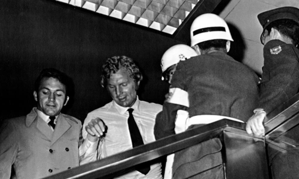 Plain clothed and uniformed policemen surround England Football captain Bobby Moore, in white shirt, as he leaves the Fuego Verde jewellery shop in Bogota, Colombia in May 1970, where it was claimed he had stolen a bracelet.