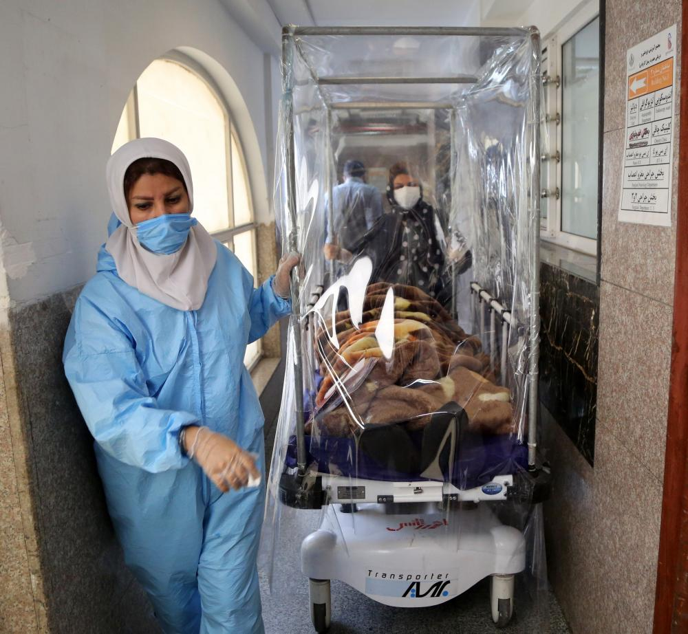 Medical workers transport a patient with Covid-19 at Rasoul Akram Hospital after a sudden surge in cases led hospitals to reach full capacity in Tehran, Iran.