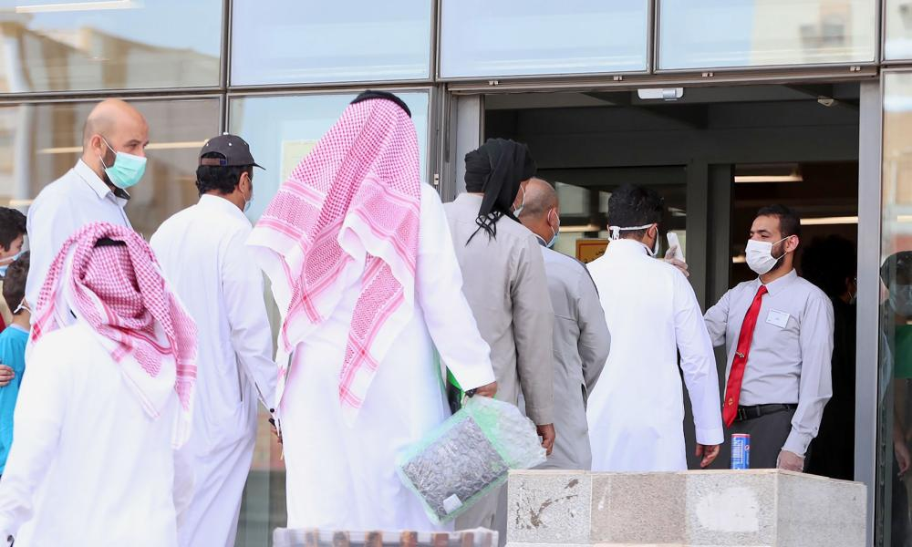 Costumers queue for a temperature check before entering a mobile shop in Saudi Arabia's holy city of Mecca.
