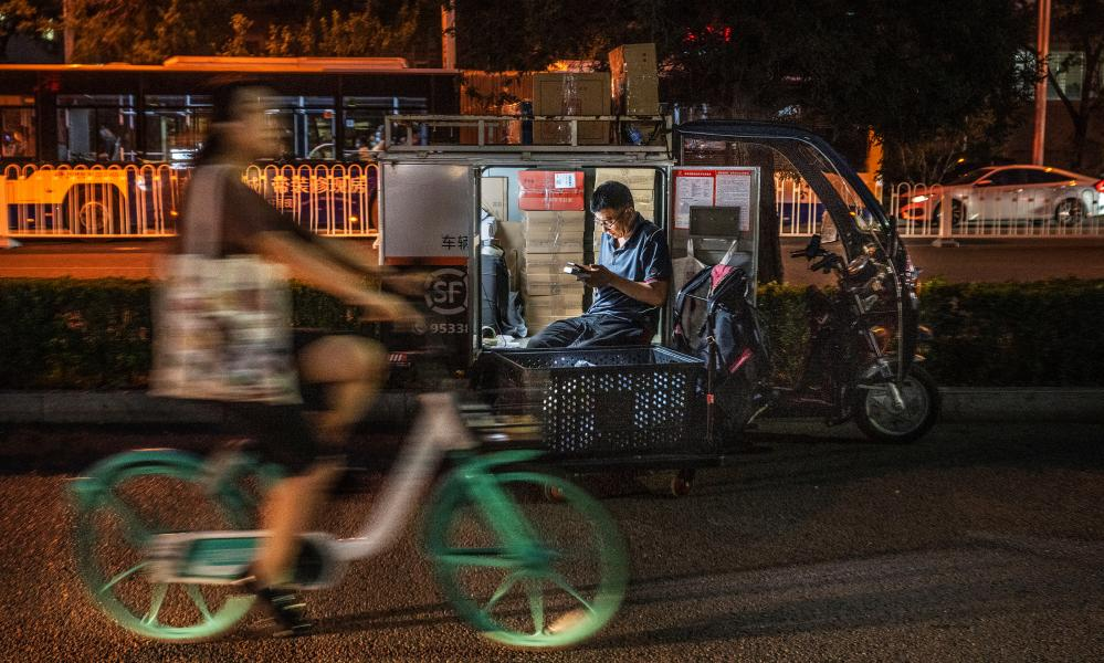 A courier sits in his vehicle as he prepares deliveries in Beijing this month.
