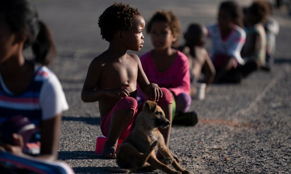 South African children sit two metres apart as they wait for a meal in the informal settlement of Masincedane, a beneficiary of the 9 Miles Project and Hope Southern Africa (HOSA) COVID-19 feeding scheme in Cape Town, South Africa, 28 April 2020.