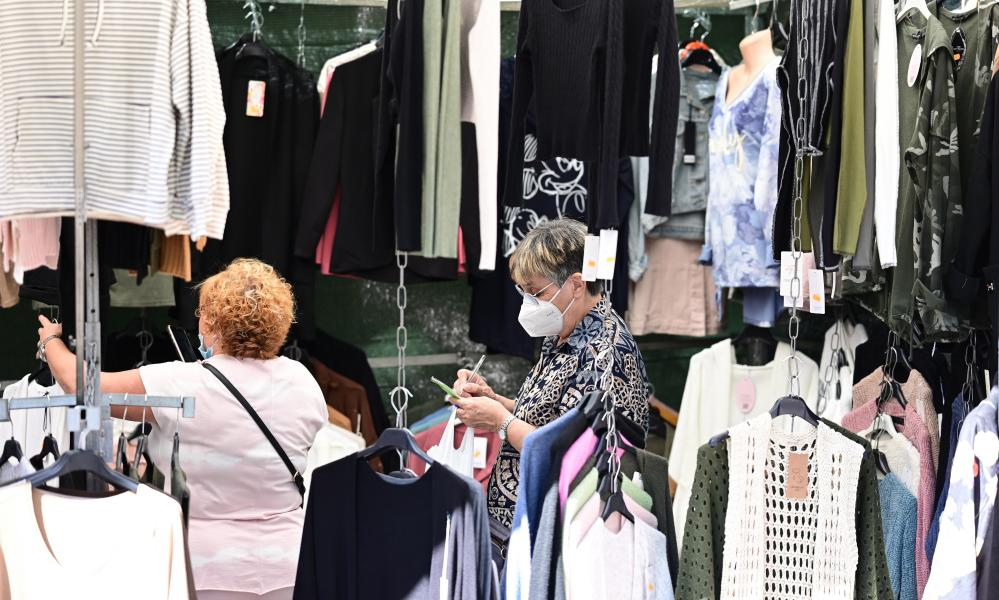 Two clients visit one of the stalls at the famous El Rastro transient flea market in downtown Madrid, Spain.