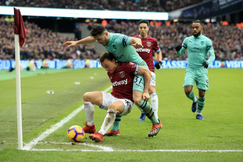Mark Noble battles for possession with Sead Kolasinac.