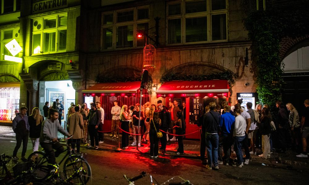 People gather in front of La Boucherie nightclub on Vestergade in Copenhagen, Denmark
