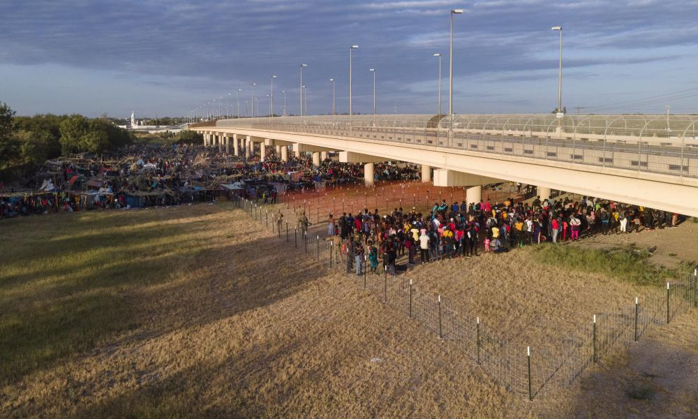 Migrants wait to get on to buses near the Rio Grande.