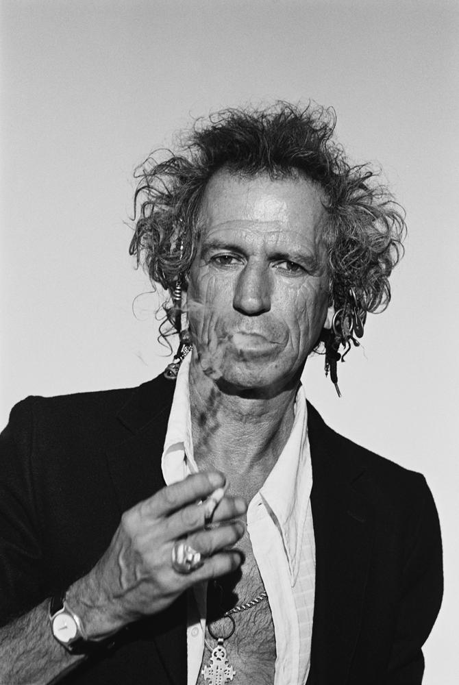 Keith Richards in a white open shirt and black jacket, holding a cigarette and smoke coming from his mouth