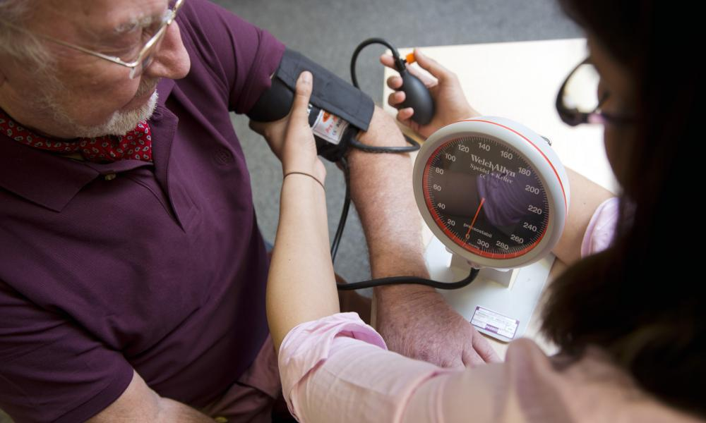 A gp gives a patient a blood pressure test