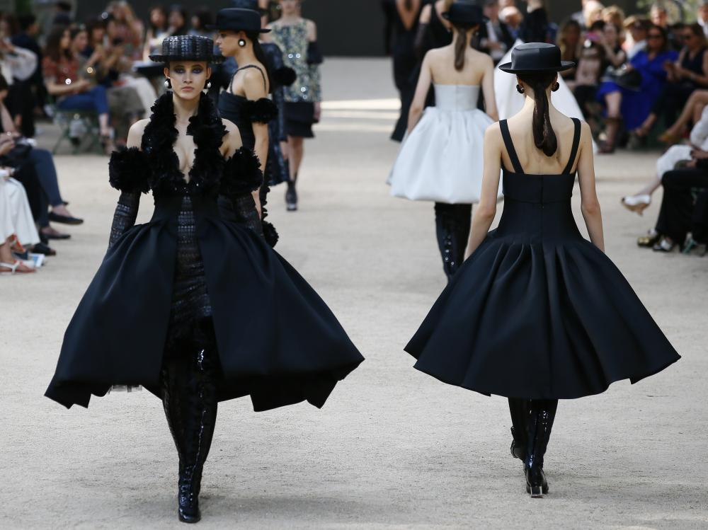 Models in circular-bottomed, black gowns on the Chanel couture autumn/winter 2017/2018 catwalk.