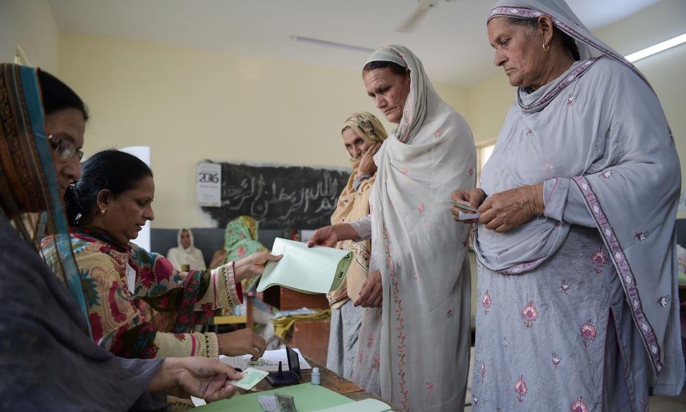 A woman receives a ballot paper in Islamabad.