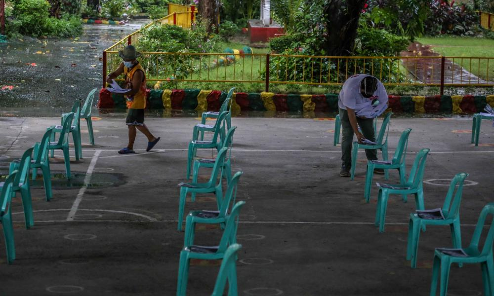 A teacher (R) and a volunteer sort distance learning materials to be picked up by parents at a school in Manila, ahead of another school year of remote lessons in the Philippines due to the pandemic.